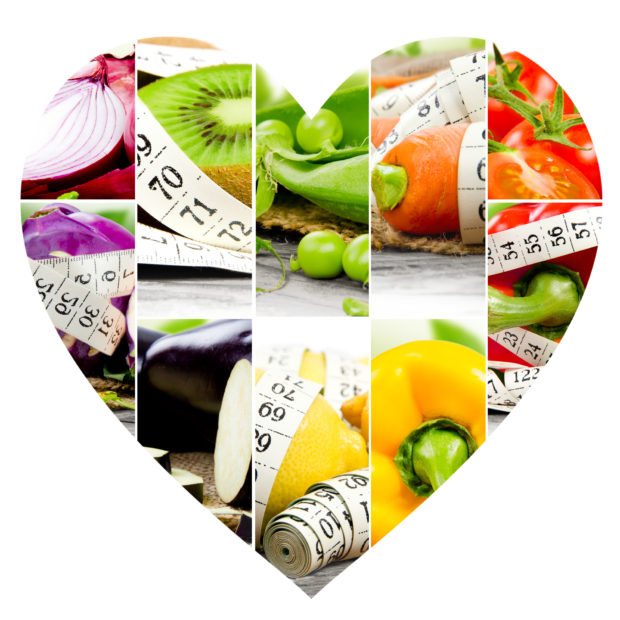 Photo of colorful fruit and vegetable mix with measuring tape, stethoscope and scale meter in a heart shape; concept of fitness