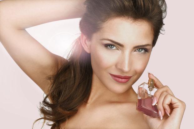 Closeup of a beautiful woman applying perfume backlight effect