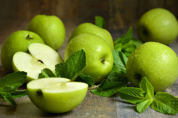 Green apples with mint leaves on wooden table.