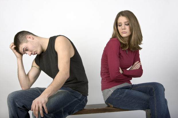 Young couple sitting on a bench seemingly in a spat.