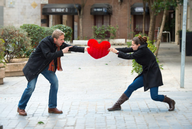young attractive couple fighting over a love hearted shaped pillow