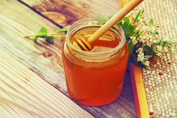 Honey in a glass jar, buckwheat flowers and bee honeycombs in a summer sunny day. Honey with flowers and honeycombs