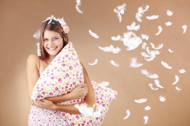 Beautiful teenage girl holding a pillow studio shot
