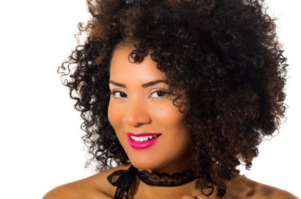 close up shot of exotic beautiful young smiling girl with dark curly hair posing isolated on white