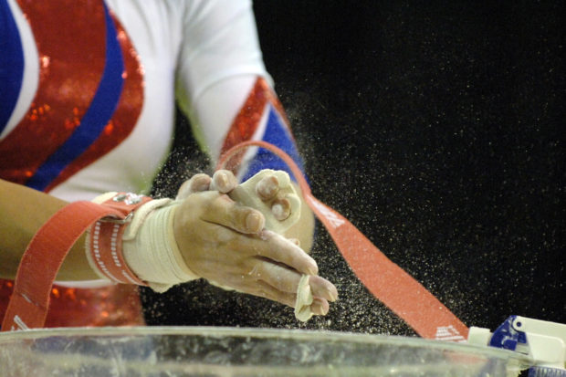 A female gymnast chalks up her hands before prefoming during competition.
