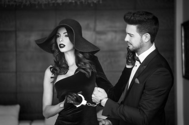 Sexy woman in hat holding young rich lover on handcuffs, black and white