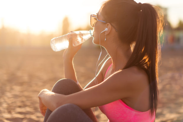 Beautiful fitness athlete woman drinking water after work out exercising on sunset evening summer in beach outdoor portrait
