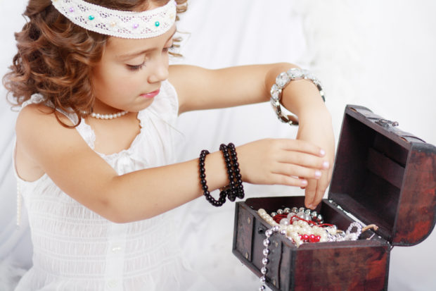 beautiful little girl plays with mother's jewelry close up