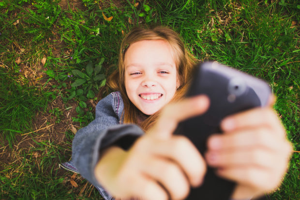 Girl laying on grass with mobile phone. Young teenager girl taking selfie using mobile phone. Cell in girls hand. Using social network.