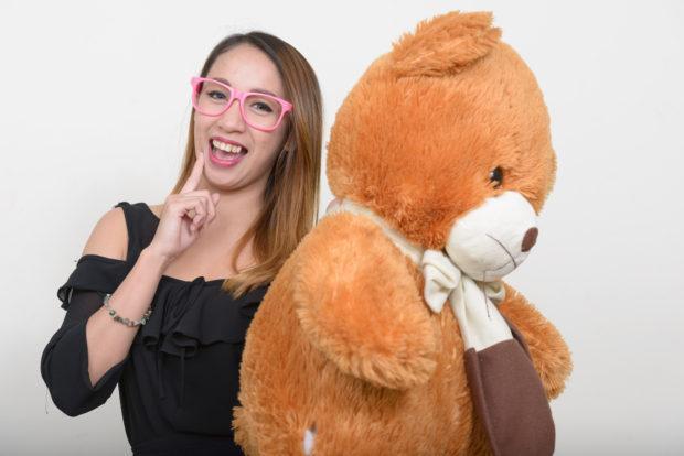 Asian nerd woman holding teddy bear