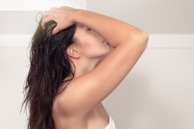 Attractive serious young woman standing in her bathroom with bare shoulders shampooing her long brown hair massaging her scalp with her fingers