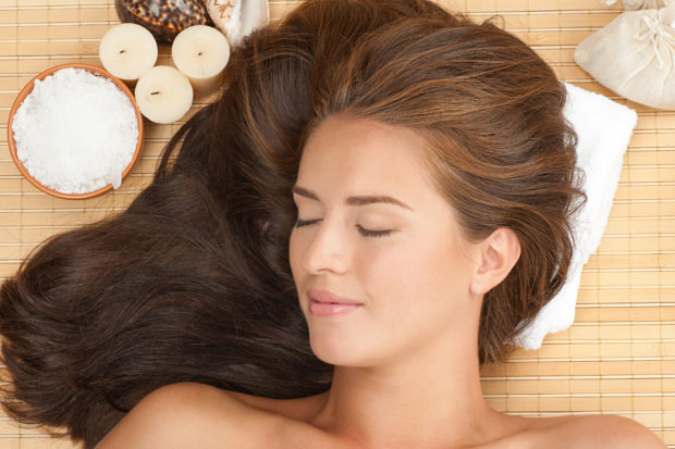 Close-up portrait of young beautiful spa woman with long brown hair lying on bamboo mat at spa salon