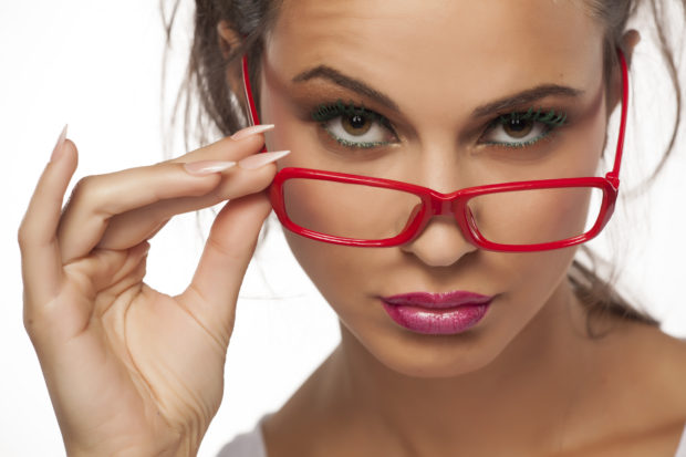 suspicious young woman with red glasses