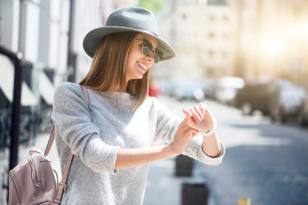 What is the time. Smiling and positive modern young woman looking at her smart watch while being outside and waiting for her friend