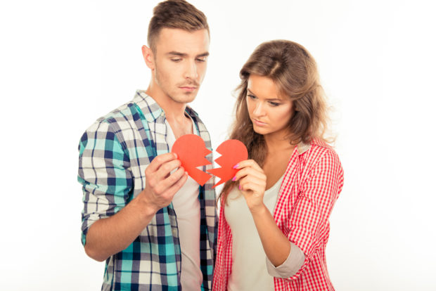 Young disconnected couple tearing paper heart