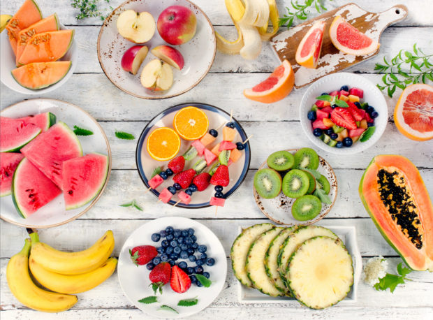 Preparing a healthy fruit salad on a wooden background. Top view