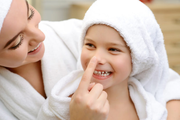 My darling. Close up of pleasant smiling daughter and loving mother having fun together after taking bath