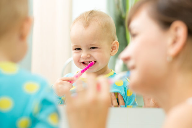 mother and kid girl look at mirror during teeth brushing