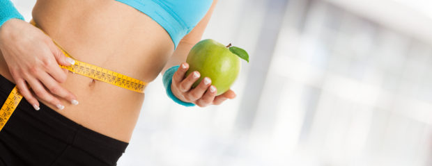 Woman holding an apple. Wide image with lots of copy-space