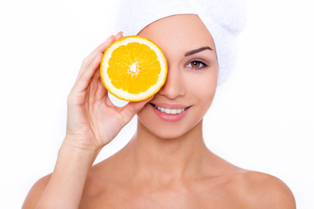 Great food for a healthy lifestyle. Beautiful young shirtless woman holding piece of orange in front of her eye while standing against white isolated background