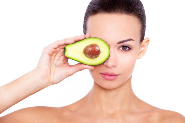 Taking care of your skin the natural way. Studio portrait of a beautiful young woman posing with an avocado over white isolated background