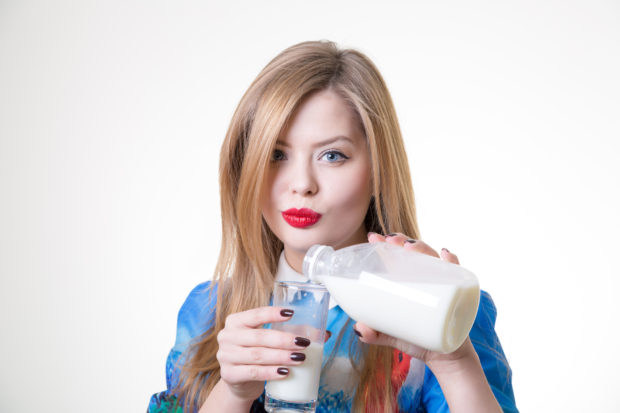 woman pouring milk in glass from bottle