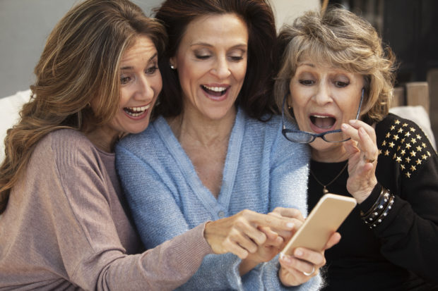 Happy group of women having fun with mobile phone outdoors
