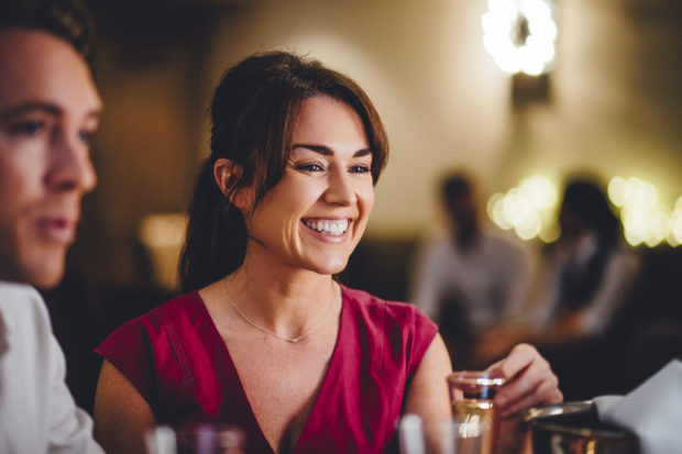 Close up of a mature woman at a restaurant. She is enjoying a glass of champagne with her friends.