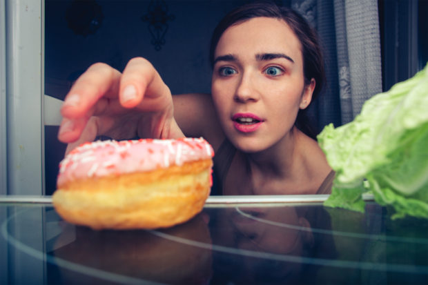 Hungry cute female reaches for donut at night near fridge