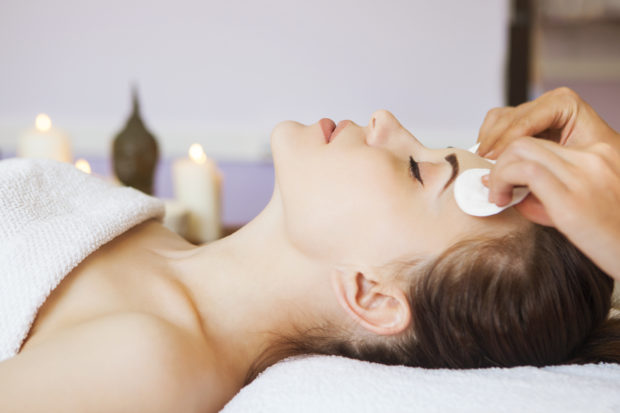 Relaxed woman with a deep cleansing nourishing face mask applied to her face. Spa treatment