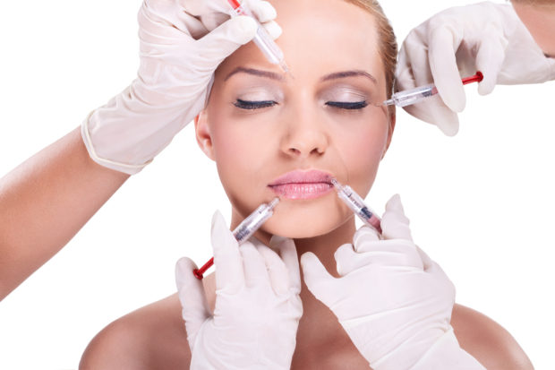 Plastic surgeons giving injection of botox