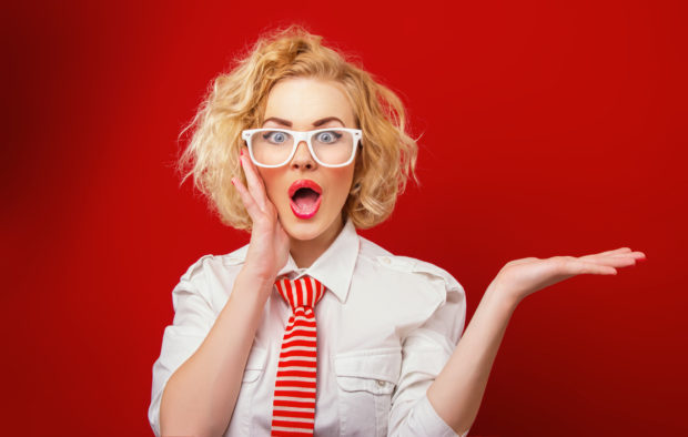 Surprised woman showing product, isolated on red background. Expression face