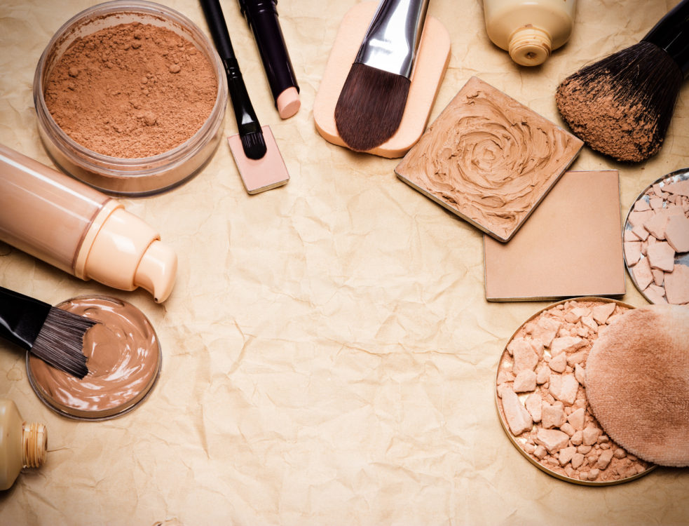 Various makeup products to even out skin tone and complexion laid out as frame on aged paper. Copy space in the center. Retro style processing