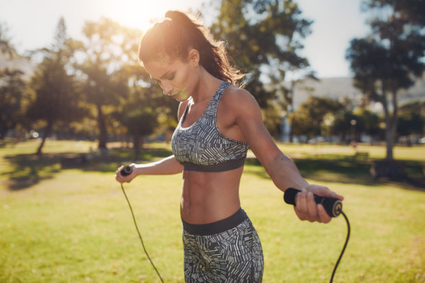 Portrait of fit young woman with jump rope in a park. Fitness female doing skipping workout outdoors on a sunny day.