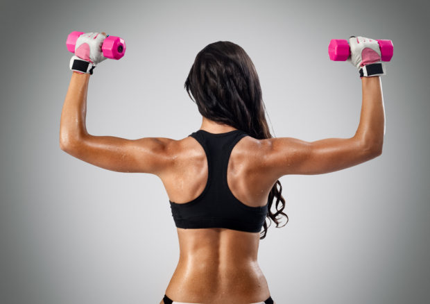 back and hands of a young sporty muscular woman working out with two dumbbells