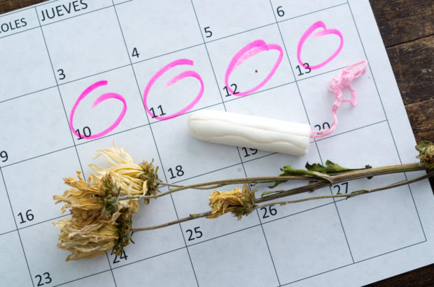 White calendar with pink circles around menstruation date period and clean tampons lying on top.