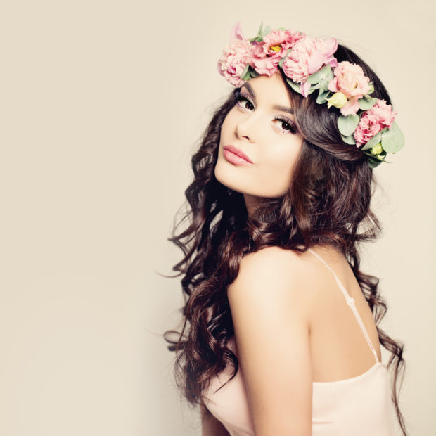 Beauty Fashion Portrait. Beautiful Woman with Curly Hair, Makeup and Flowers Wreath