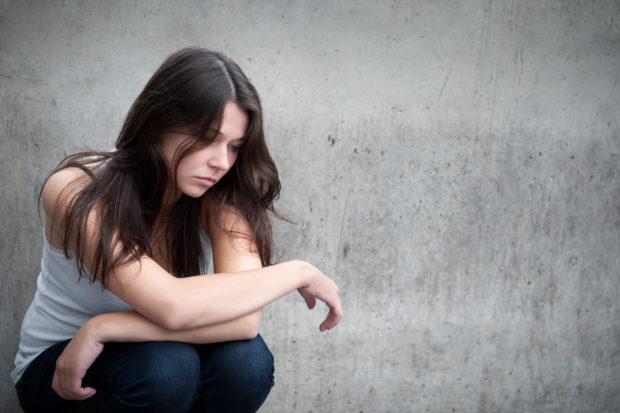 Portrait eines nachdenklichen, traurigen Mädchens vor einer grauen Mauer
