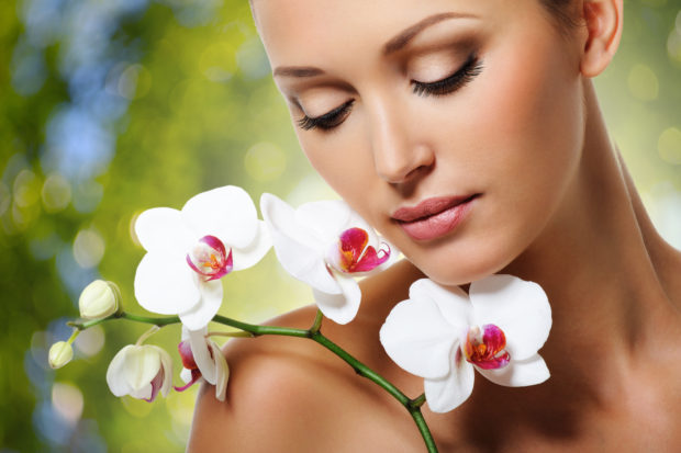 Beauty face of beautiful woman with a white orchid flower. Skin care treatment. Green nature background