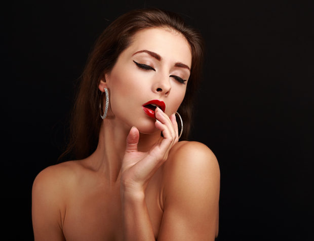 Hot sexy exciting woman with hand near red lips on black background