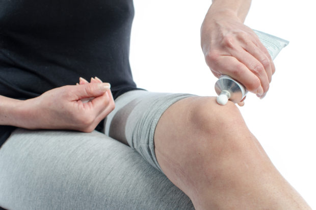 Woman putting relaxing cream on her knee