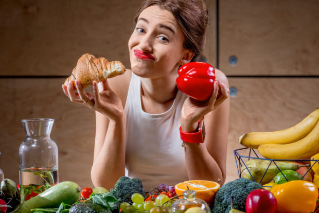 Young woman choosing between sweet croissant and healthy fresh food. Worry about calories and weight