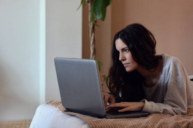 woman looking at her laptop in bed in the morning