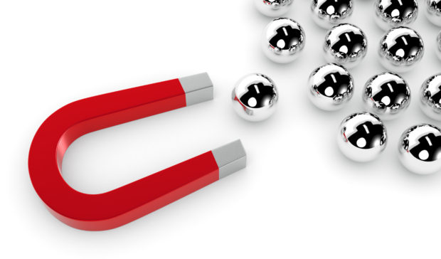 one magnet and a group of spheres. one of the spheres is pulled by the magnet, concept of competition and leadership (3d render)