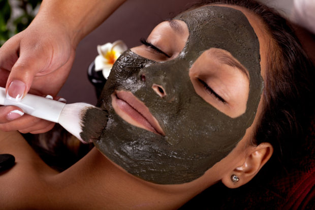 Cosmetologist doing massage on the woman's face in spa salon.