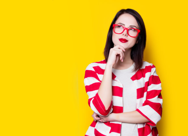 Portrait of a yung style woman in glasses on yellow background