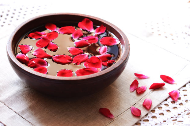 Rustic wooden bowl with floating red rose petals for relaxation