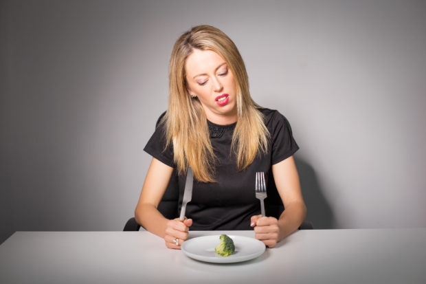 Woman on diet eating broccoli