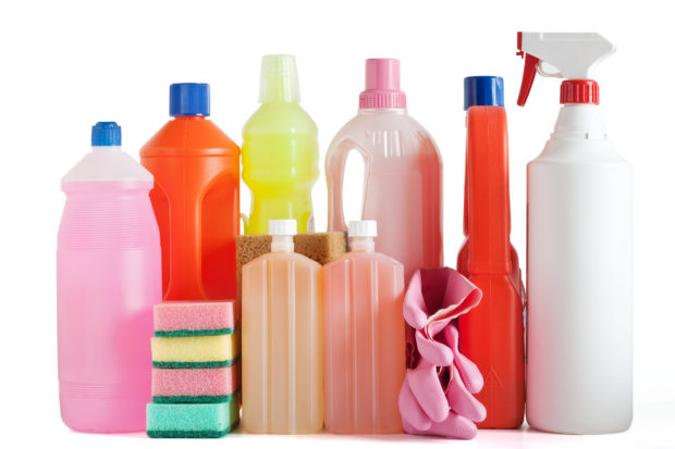 Colored plastic detergent bottles with sponges and gloves isolated on white background with clipping path
