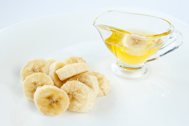 Banana slices with honey in a glass gravy boat. Healthy sweet dessert in a white plate